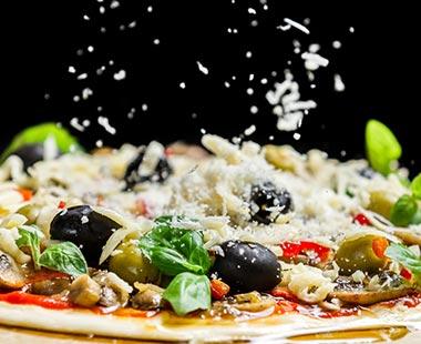 פיזור פרמזן מעל פיצה